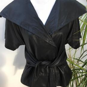 Varetype: Læderjakke Farve: Sort  Fed skindjakke med korte ærmer og slå-om bælte. Flot udover en bluse/skjorte - giver en super fin figur.