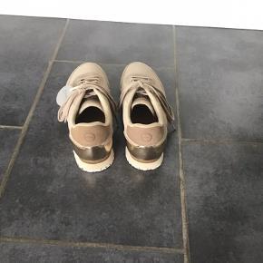 Helt nye Woden sneakers i beige med bronze/guld på hælen. De er desværre et nr. for store til mig.