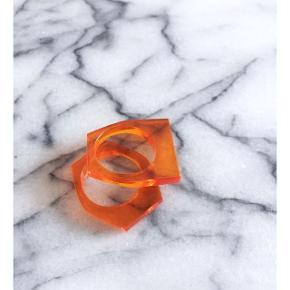 Orange plexiglas ringe, størrelse M. Købt på arkitektskolens julemarked. Sender gerne med DAO :)