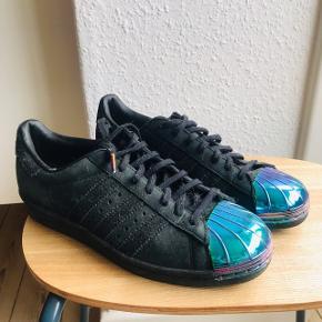 Super fede Adidas Superstar 80S i str. 6 eller 39 2/3 👟 nyprisen var 1050 kr i Rezet Store. De er brugt max 5 gange, og derfor i rigtig god stand. Virkelig fede med den metalliske snude og i lækkert, velholdt skind.   Bemærk - afhentes ved Harald Jensens plads eller sendes med dao. Bytter ikke 🌸  💫 Sneakers sko Adidas sneaks sorte sneakers kicks læder lædersko metal metallic metalliske metallisk blå
