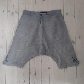 Fede shorts med drop crotch fra Henrik Vibskov. Shortsene er lavet i ternet stof med blandede mønstre og bordeaux detaljer. De har stiklommer i siderne og én baglomme.  100 % bomuld.  Ekstra knap medfølger.