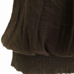 Sort top uden ærmer fra Pulz str XL i krøllet look med sølvnitter rundt i halsen, som adskilles af hulmønster. Bredt elastik-stykke nederst.  Lukkes med tre knapper på ryggen. Længde fra skulder er 80 cm, og brystmålet er 110 cm. Fremstillet af 86% viscose og 14% polyamid.