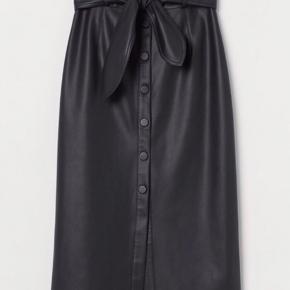 Super fed nederdel i imiteret læder fra H&M 🖤   Har høj talje med bredt, aftageligt bindebælte og lukkes foran med knapper.  Materiale: 100% polyester.   Str. 36/S (kan også passes af en M, vurderer jeg).   Nypris 250 kr.  Sælges for 100 kr. Prisen er fast, da nederdelen kun er gået med et par gange og derfor fremstår som ny.