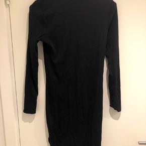 Højhalset ribbed tætsiddende kjole med lille slis. 96% polyamid, 4% elastan.