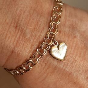 Super fint Armbånd i 14 karat massiv guld med hjertevedhæng sælges. Model Bismark. L: ca. 16,5 cm. B: 7 mm. Armlænken er med kasselås og sikkerhedskæde. Velholdt og i orden. Vægt ca. 9-10 gr. Stemplet 14K mester: V.    ** Smykker guld - 14 karat - Armlænke guld - Bismark guld - Armbånd guld **