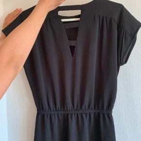 Sort kjole fra Vero Moda. Brugt en enkelt gang. Snører i taljen. 2 lommer foran Længden er 94 cm.