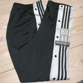 Adidas adibreak sorte bukser med hvid stribe. I pæn stand, almindelige brugsspor på det nederste af benene som ses på billedet.