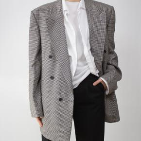HOUNDSTOOTH ULD BLAZER     - Black & White     - 100% Wool     - Made in England     - Shoulders: 49cm     - Chest: 120cm     - Length: 81cm     - Sleeve: 64cm      - Size: S-XL  Model is 170cm tall.