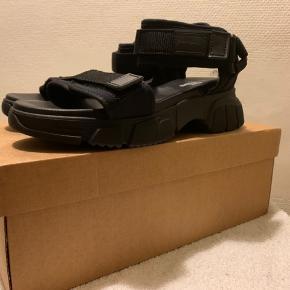 Sorte UO / Iets Frans lidt chunky sandals med regulerbare remme i str 38 Længde fra snude til hælkap ca 25 cm Hæl målt bagerst ca 4 cm og sål foran ca 2 cm (Købt sidste år til 500+) Har også ubrugt par i 37 / se evt anden annonce! Hvis afhent 225