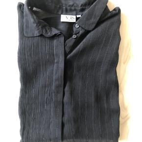 Lækker let skjorte i sort tynd stof og med glimmer tråde i stoffet. Den er rigtig sort, lyset driller lidt.   Mærke: Vrs.  Størrelse: L/ Xl.  (Mærket Xl, men brugt som oversize i L).  Stand: Næsten som ny.  Nypris: 180 kr.  Pris: 25 kr.   Sender gerne med Postnord, Gls og Dao.