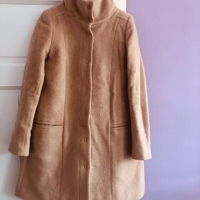60% Virgin uld, 28% mohair uld, 12% polyester.  A-form uld frakke med stærke trykknapperne og dybe lommer.