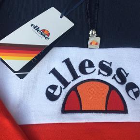 Rigtig lækker Ellesse colour block hoodie med half zip. Købt den 22. juni 2018. Skulle have været byttet til større størrelse, men er over fristen for retur retten pga. ferie. Modellen er eftertragtet og udsolgt ved Asos hvor den er købt.