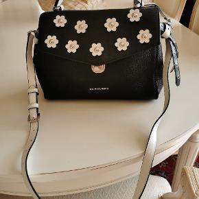 Fantastisk flot taske fra Michael Kors i sort med hvide blomster. Tasken er af læder og har en aftagelig skulderrem. Den er aldrig brugt og fremstår som ny.  Sælges for 1000,- Nypris 2800,-  Sendes på købers regning.