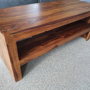 Helt nyt sofabord sælges.  Fejlkøb.  I mørkt massivt Sheesham-træ. Nypris i danske butikker 2000-2500 kr.  Stadig i original indpakning/kasse   Mål: Højde: 45 cm Længde: 110 cm Brede: 45 cm  Højde til bund af hylde: 16,5 cm Hylde top: 22,5 cm  Skal afhentes i 6600 Vejen eller kan leveres til nærområdet.