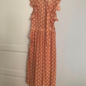 Super fin og let maxi kjole med bindebånd. Orange med hvide prikker. Størrelse 8 svarende til str. 36. Aldrig brugt.  Jeg foretrækker at handle via Trendsales og sende med DAO. Alternativt via MobilePay.  Køber betaler gebyr og fragt.
