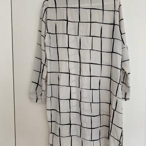 Lang skjorte med sort ternet print. Brugt men stadig i fin stand