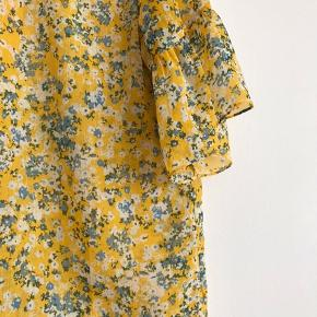 Fin gul top med blomster fra Samsøe Samsøe. Der står ikke størrelse på men svarer til en str. S. Brugt en gang fremstår derfor i god stand.   Kan afhentes i Ørestad eller sendes på købers regning.
