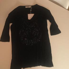Varetype: Kaisa Tee Farve: Sort Oprindelig købspris: 400 kr.  Sort bluse med 3/4 ærmer og simili sten foran, aldrig brugt