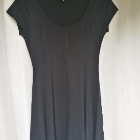 Sort kjole i bomuld. Med markeret talje. Meget behagelig at have på.  Kjolen er brugt én gang.