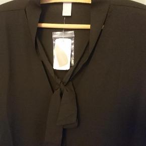 Fin skjorte fra Forever 21 - aldrig brugt, stadig med tags. Med V-udskæring og et bindebånd, som kan hænge løst eller som kan bindes som en sløjfe, i en løs knude el.lign. En afslappet (og tildækket) måde at være elegant på, f.eks. til fest.  Aldrig brugt - stadig med mærke.  Sælges for kun 50 kr plus porto (37 kr som pakke med DAO).  Ja - porto er blevet latterligt dyrt - køb evt. flere ting af mig og betal kun porto én gang for det hele (-:   --- 0 ---  Se også alle de andre ting i sort, sølv, grå og guld, jeg sælger  skjorte med bindebånd Farve: Sort