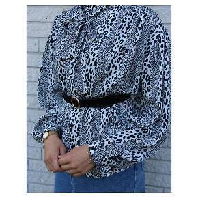 Black and White! Vintage silkeskjorte med mellem skulderpuder, og en elegant sløjfe ved kraven. Skjorten kan bruges til hverdag og fest. Fejler intet. Fits: s-xl.