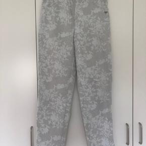 De velkendte Lau Rie lange bukser med stræk i. Bred elastik i taljen, 2 lommer foran i lys grå med lyst blomstret mønster i stoffet.