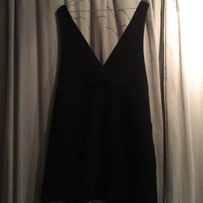 Kjole med dyb udskæring. Bruges med T-shirt, rullekrave eller skjorte under. Lommer i.