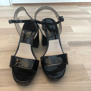 Stiletter/høje sandaler i sort lak fra Zara. De er kun gået i en enkelt gang, da jeg har for brede fødder til dem. De ser stadig nye ud.
