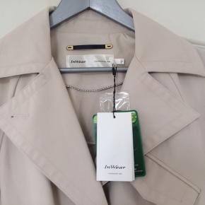 NYESTE FORÅRSMODE... JossIW Trenchcoat, style 30105117, farven hedder French Nougat, pasformen er Classic/regular fit, længde 117cm...(stor i str.)55% polyamid/45% bomuld... bionic-finish ECO(smuds-og vandafvisende, åndbar og hurtigtørrende). Aldrig brugt, stadig med prismærke...pris + porto(DAO)