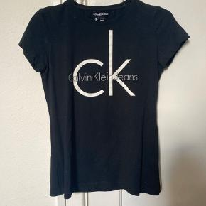 Sælger min smukke og helt ny Calvin Klein Jeans tee / T-shirt  Den er prøvet på nogle gange, men er aldrig blevet decideret brugt. Den er deraf i perfekt stand, og har ingen slidtegn. ☀️  Str. S - Small (Kan sagtens passes af en xs eller en mindre medium) - dets materiale er stretchy  Dustbag haves vidstnok et sted, måske også kvit   NP: 400kr Mp: BYD   OBS:‼️ sælger lige nu - billigt - ud af en masse forskelligt mærketøj, tjek det ud! 🔆 🍒