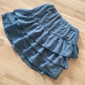 Flot lyseblå POMPdeLUX nederdel med sorte prikker str 134/140 med regulerbar elastik i livet. Også brugt samtidig med str 128. Brugt få gange. .  Sender gerne