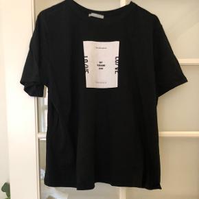Sort t shirt med print fra Zara. Stor i str så passer en xl også. Eller oversize.