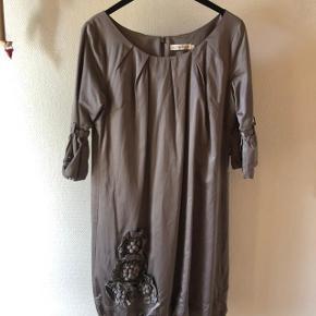Kjole fra By Groth. Str. xl. Nypris 1500 kr. Den smukkeste kjole i beige med mange smukke detaljer. Blomster forneden. 3/4 ærmer med spænder. Bomuld/polyester. Jeg er 173 cm. høj, og den går mig til under knæene. Brugt og vasket få gange.