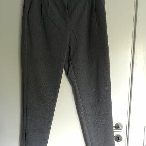 Bukserne er kun brugt 2 gange og vasket en enkelt gang og fremstår derfor nærmest som nye. Stoffet er blødt og buksen har elastik bagpå i taljen, hvilket giver en god pasform.