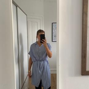 Skjortekjole fra H&M i midi-længde. Hvid og blåstribet. Den nederste knap er faldet af. Kjolen er brugt og vasket omkring 10 gange. Passer xs/s/m.