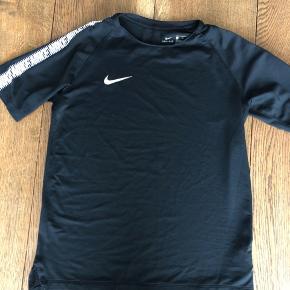 Sort Dry-Fit t-shirt med Nike mønster på ærmerne. Kun brugt få gange.