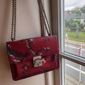 Sælger den fine røde mango taske med smuk mønster! Tasken har en fed kæde hang på i sølv. Sælger den udelukkende fordi jeg ikke får den brugt. Tasken er i en passende str kan bruge til byen eller til hverdag🌸🌸
