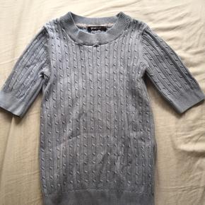 Lyseblå strikket trøje fra Gina Tricot. Trøjen sidder tæt og følger kroppen fint uden at stramme.