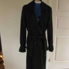 Flot overgangs frakke fra Gestuz Den er sort med hvide striber.  63% polyeste 33% viscose  4% elasten Den er dejlig lun