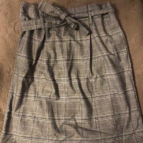 Kun prøvet på. Så fin ternet nederdel. Går lidt lige over knæet (er 170 høj). Font bindebånd i.