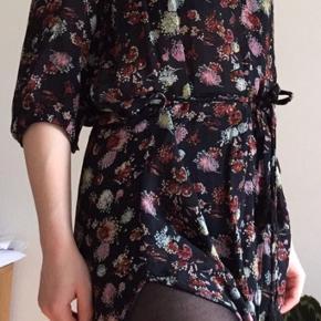Skjorte/kjole i mørkeblåt stof med flerfarvet blomstermønster. Har skulderpuder og bindebånd med frynser. 100% viscose.