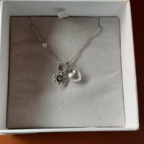 Smuk Blossom halskæde i rhodineret sølv med hjerte og blomster vedhæng samt med en zirkonia sten, måler 80 cm. Er brugt meget få gange, er som NY. Se også tilhørende ørestikker. Sendes hurtigt ved køb, også gerne samlet :-)