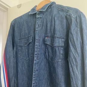 Lækker skjorte i relaxed fit. Fed detalje med bånd i klassiske TH farver på ærmer og ryg. Brugt max 3 gange