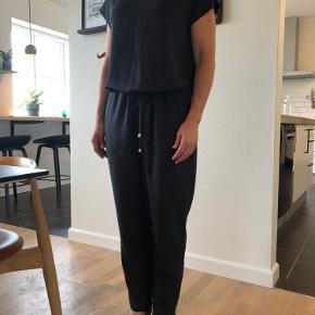 Den klassiske buksedragt fra Mads Nørgaard model cavi i mørk grå. Buksedragten er meget rummelig i modellen