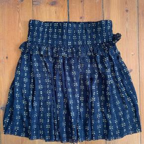 Kort mørkeblå nederdel med brodering i guld og flæse fra H&M i str.S. Aldrig brugt.