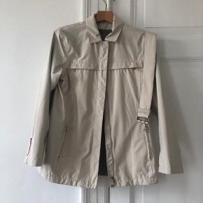 Sindssyg lækker overgangsjakke fra Prada, med bælte til taljen. To små huller ved skulderen men ellers intet slid.