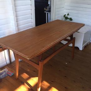 Kombineret sofabord og spisebord.  Teak bord med udtræk og hæve sænke funktion. Du kan derfor både bruge det som sofa- og spisebord. Midterste plade (selve bordet når det ikke er udslået) trænger til en gang olie, men ellers er der ikke tydelige tegn på slid   Måler: 140 cm langt 60 cm bredt 70 cm højt (når det er slået op som spisebord) 60 cm højt (som sofabord)