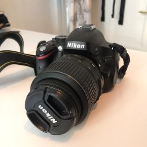 """Nikon D5100-spejlreflekskamera med 16,2 megapixels, 3"""" vippeskærm og linse 18-55mm 1:3.5-5.6G VR. I god stand og virker upåklageligt. Der medfølger batteri, oplader (med amerikansk stik, men du får en adapter med), manual, 2 SD-kort, 2 ledninger, og Ruggard-kamerataske. Hvis du har nogen spørgsmål, er du velkommen til at skrive :"""
