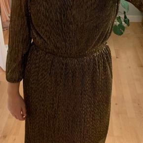 Super fin guld/bronze kjole fra Gestuz. Brugte ganske få gange og i rigtig fin stand. Kan både bruge med åben eller lukket knap i halsen.
