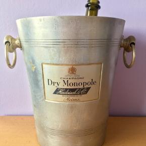 """27-150. Heidsieck Champagnekøler. """"By appointment to her Majesty The Queen Purveyors of Champagne. Dry Monopole  Heidsieck & Co. Maison Fondée en 1785 Reims."""" Antik aluminium champagnekøler med flot emalje skilt dobbeltsidet med producentens logo. Fin stand med flot patina. Holder 2 flasker.  HxØ: 24,5x21 cm. Med hanke 27 cm. 678g.  Sælges kun 799kr.   Ægte fransk køler fra hæderkronede Champagne producent. Perfekt til alle store fester/begivenheder som et festligt indslag: nytår, fødselsdage, dimission, studenterfest, svendegilde, bryllup, konfirmation, fernisering, reception, åbningsevent, gallapremiere & romantisk hyggeaften/middage med kæresten.  Gaven til ham/hende som har alt.   Fra røgfri, børnefri & dyrefri hjem. Flasker følger IKKE med. Se mine andre annoncer: flasker op til 15 L, champagnesabler, vinglas & Champagnekølere. Kan skaffe andre typer, så spørg om det."""